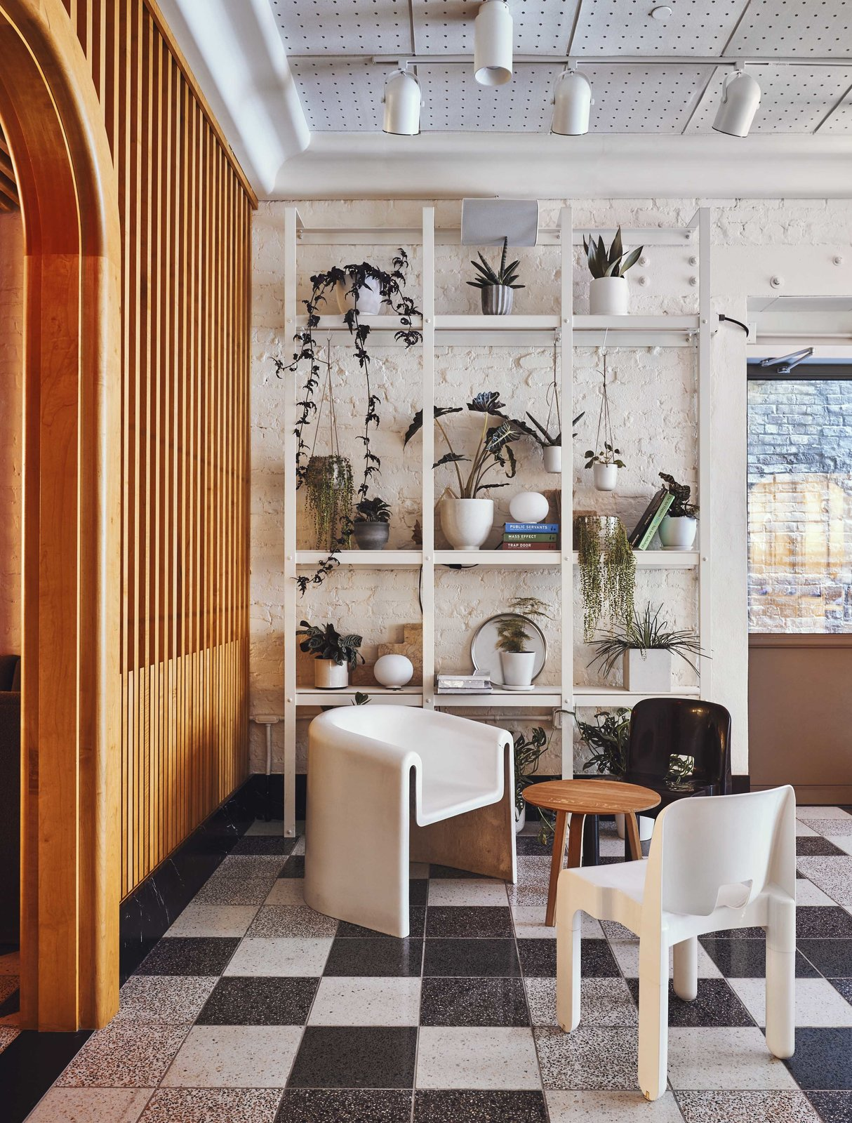 Living Room, Ceiling Lighting, Chair, Concrete Floor, Shelves, Terrazzo Floor, End Tables, and Track Lighting One of the sitting areas in the lobby immersed in plants and natural light.  Photo 3 of 9 in Ace Hotel's Sister City Opens in New York—and it's a Beaut