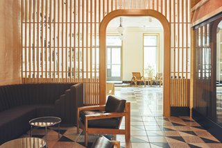 A latticed wall with an arched door partitions the lobby.