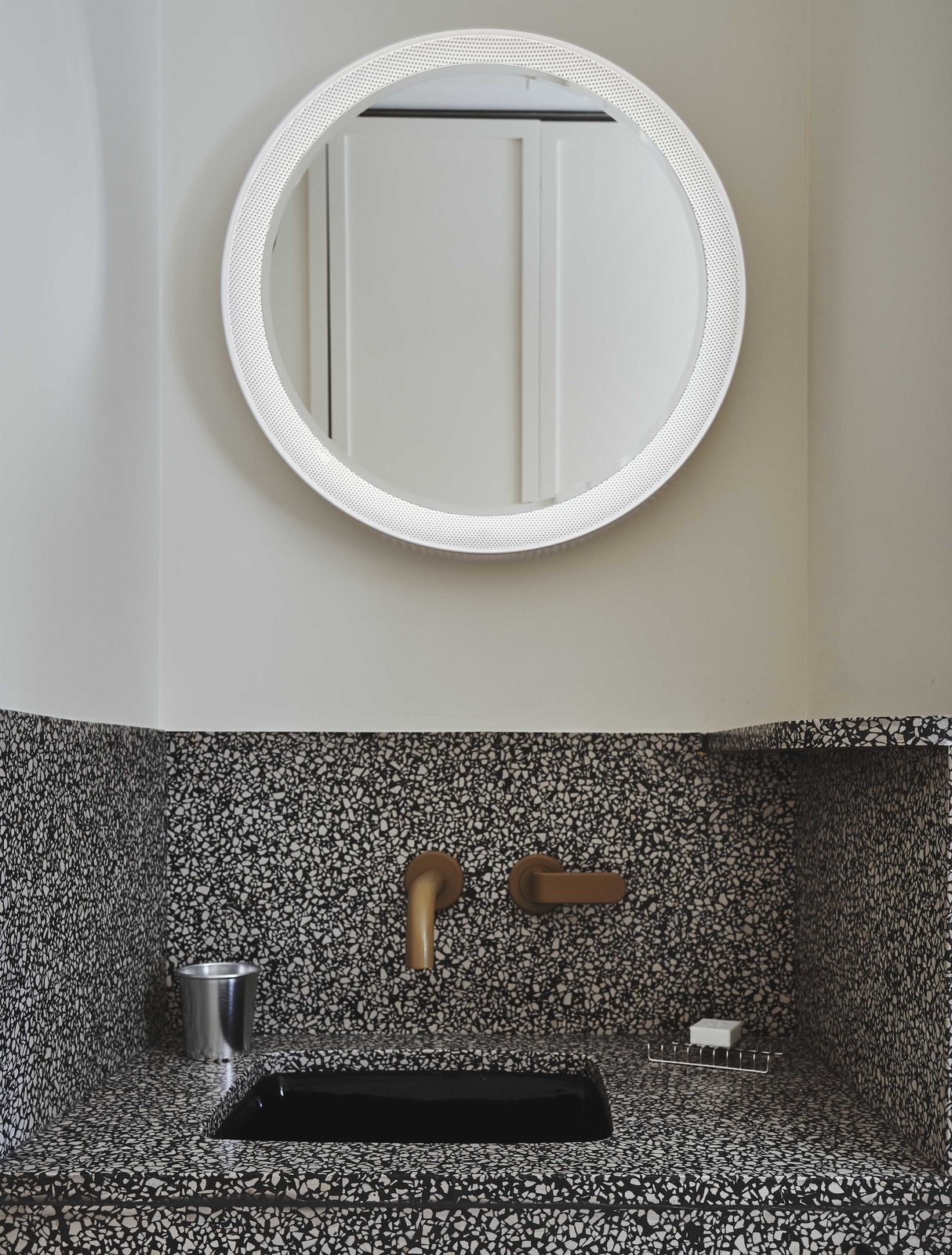 Bath, Wall, Stone, Accent, Undermount, and Glass Tile The intricate, speckled design of the vanity is paired with clean white walls and an illuminated circular mirror.  Bath Undermount Stone Photos from Ace Hotel's Sister City Opens in New York—and it's a Beaut