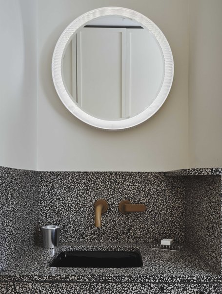 The intricate, speckled design of the vanity is paired with clean white walls and an illuminated circular mirror.