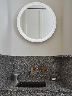 The intricate, speckled design of the vanity is paired with clean, white walls and an illuminated, circular mirror.
