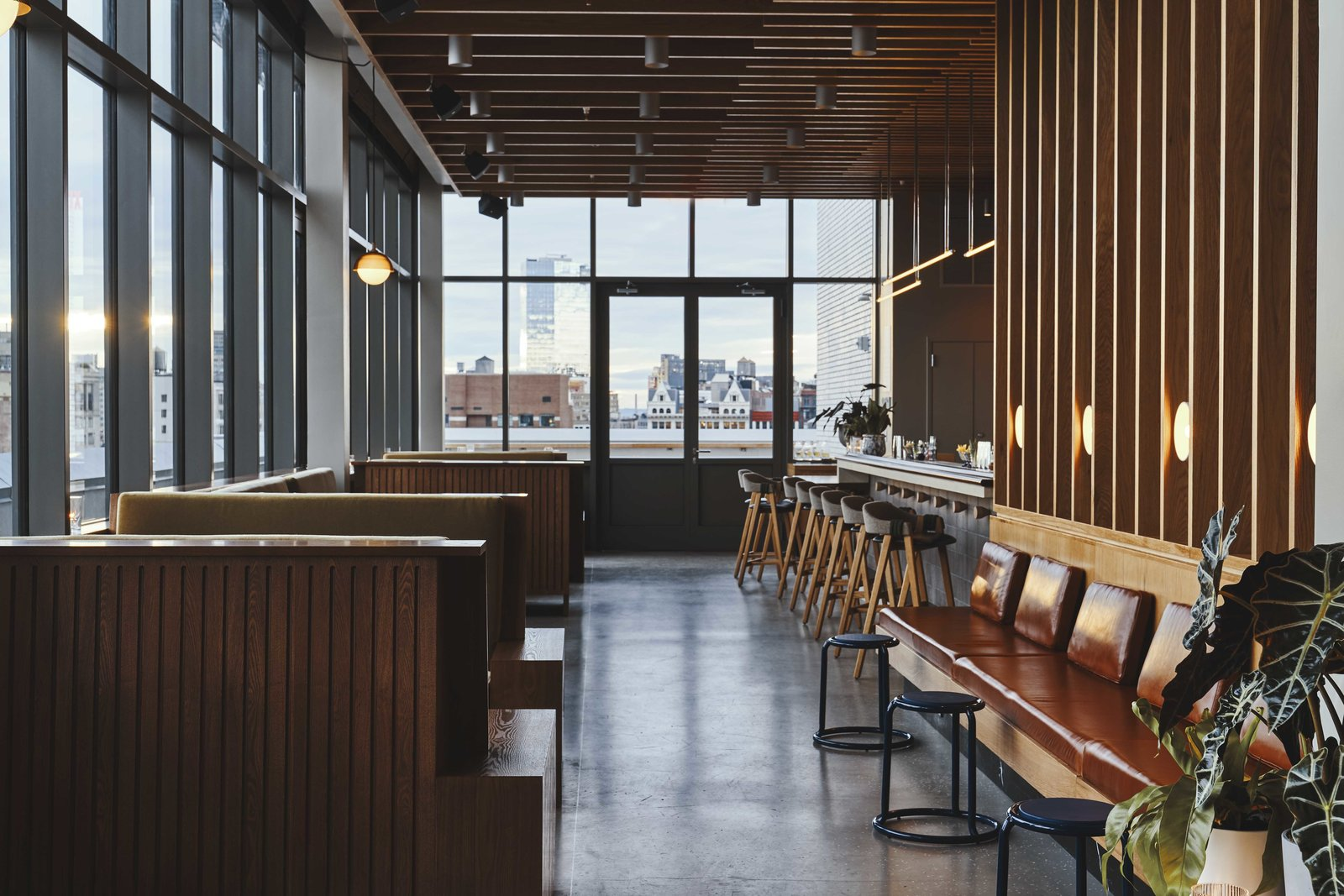 Dining, Ceiling, Bench, Table, Bar, Lamps, Chair, Stools, Concrete, Wall, Accent, Track, and Pendant Last Night is permeated with wood slats, creating a warm space to sip and mingle.  Best Dining Accent Wall Ceiling Lamps Photos from Ace Hotel's Sister City Opens in New York—and it's a Beaut