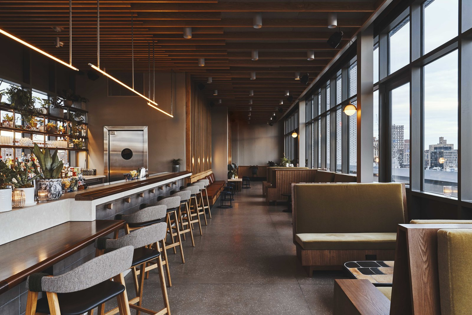 Dining, Ceiling, Chair, Bench, Concrete, Stools, Table, Bar, Wall, Track, Terrazzo, and Pendant While the design in the bar remains clean, the tones are moodier with an added touch of glam.  Best Dining Pendant Wall Photos from Ace Hotel's Sister City Opens in New York—and it's a Beaut