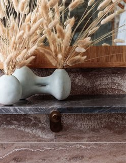 A vase filled with fluffy reeds lends a bit of softness to the stone bathroom.