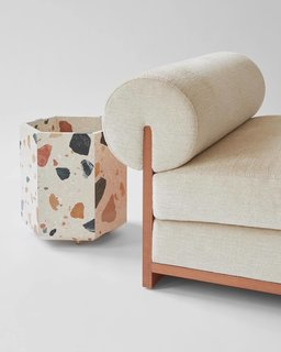 A slipper chair version of Moving Mountains' chaise next to Fort Standard's Marmoreal planter.