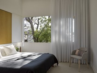 The soothing bedroom juts out slightly from the rest of the house, creating a courtyard outside.