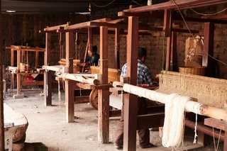 An array of looms allows weavers to work in tandem.