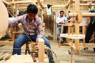 Artisans weave in a workshop.