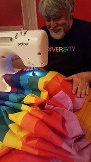Baker sewing the nine-color diversity flag.