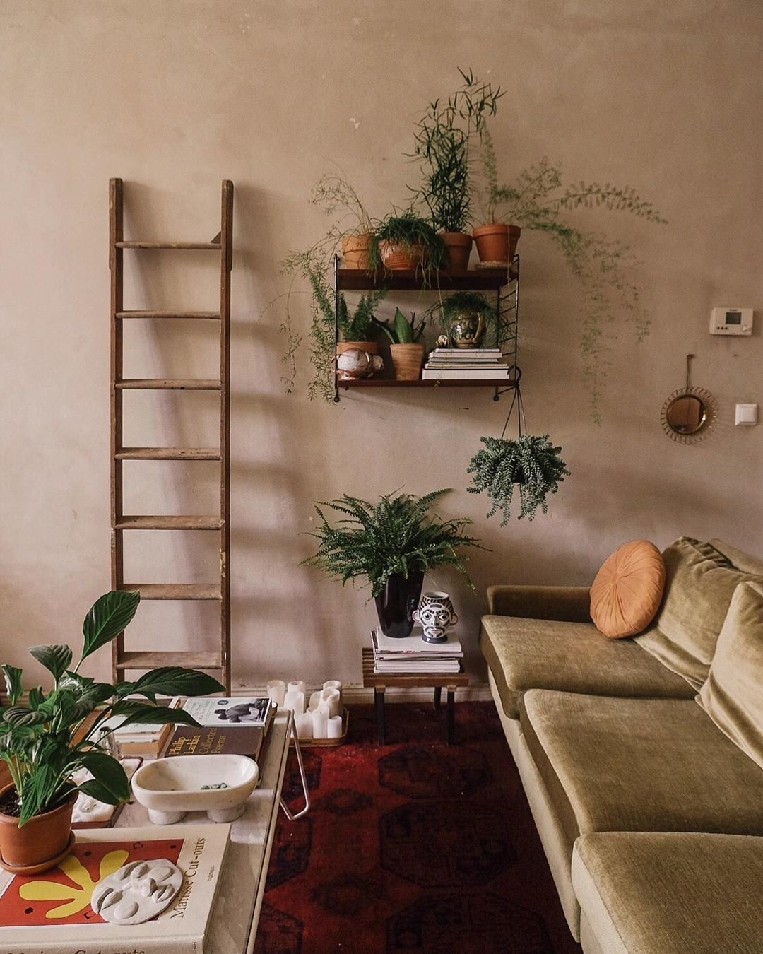 Living Room, Coffee Tables, Medium Hardwood Floor, End Tables, Sofa, and Rug Floor Theodora's Berlin abode has all the artsy feels.  Photos from 9 Plant-Filled Abodes You Should Follow on Instagram Right Now