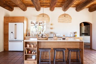 The main kitchen holds Wayfair counter stools, small dining tables and chairs, sink, faucet, and light fixtures; custom cabinetry by Café Appliances and Fire on the Mesa; and a hanging fruit basket by Xinh and Co.