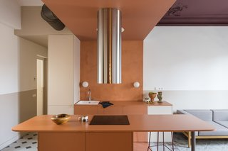 A steel kitchen fan cylinder stands as the anchor in the kitchen with white, plastic dome overhead disguising a spotlight to replace a ceiling lamp. Small globe sconces provide extra light on the backsplash.