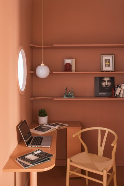 Tucked in a recessed space is the studio, opposite the kitchen. A bespoke desk provides just the right amount of work space. Shelves are cut in a circular shape to allow a pendant lamp to hang through them. A porthole window brings a dash of natural light into the space.