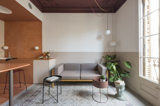 The living room post transformation has a Kettal Landscape sofa with mustard frame and mink cushions, a planter by FermLiving, and a Handvärk lamp by Studio Floor.