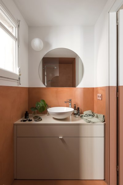 The bathroom is swathed in the same brick red micro-cement.