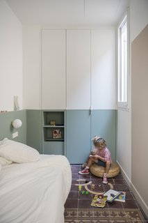 The children's room has a built-in wardrobe that follows the wall colors.