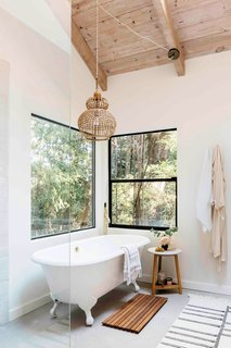 The art of bathing extends beyond the outdoor spa—a standalone soaking tub in the master bath looks out to the redwoods. The lighting fixtures are from Anthropologie, Serena & Lily, and Warmly.