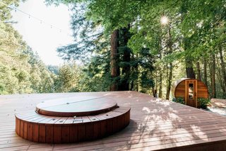 The Northern Lights outdoor hot tub and sauna top off this wooded retreat.