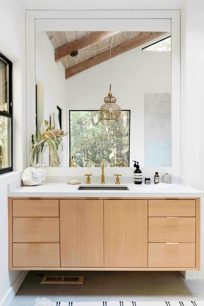 This bathroom features a custom-designed vanity with Kohler fixtures.