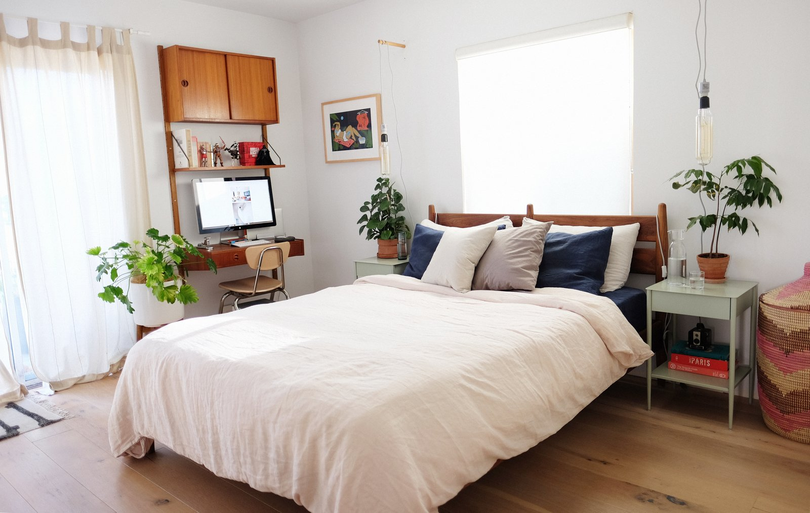 Bedroom, Bed, Chair, Night Stands, Medium Hardwood, Pendant, and Ceiling Their Room & Board bed is swathed in sheets from Parachute Home.   Bedroom Pendant Chair Bed Photos from My House: How a Designer Couple Are Weathering the Pandemic in Their Berkeley Home