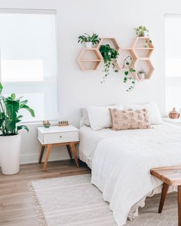 Jules has been taking mornings a bit slower, allowing herself some extra sleep in her cozy West Elm bed and Parachute bedding. Above, handmade honeycomb shelves bring more of the outdoors in with some cascading plants.