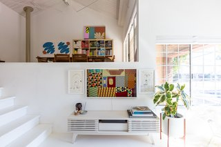 The home has large warehouse windows that flood the space with light, ideal for their array of plants and also providing an airy palette for their art collection. On either side of a Samsung Frame TV are Riso prints by Jeffrey Cheung. Just below is an assortment of ceramics including a piece by Tyler's sister. A Case Study Modernica Planter adds a touch of greenery.