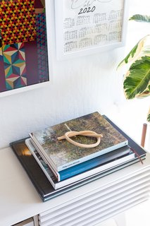The home is peppered with vignettes—here, a wood knot by artist Katie Gong tops a stack of art books.
