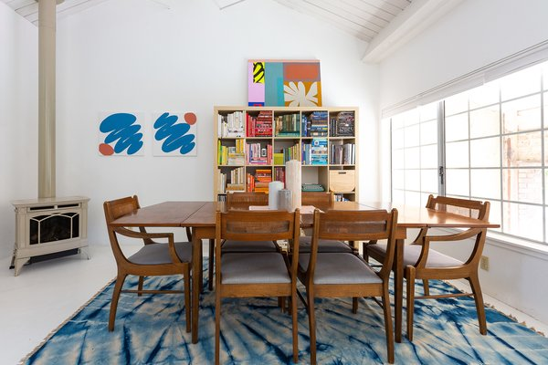 A vintage table and chairs ground the dining room, which features art by Chaz Bear (also known as Chazwick Bundick).