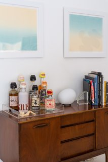 A Gregg Table Lamp by Foscarini sits atop a vintage credenza that the couple use as a bar. The gradient landscape diptych prints above are by Erin.