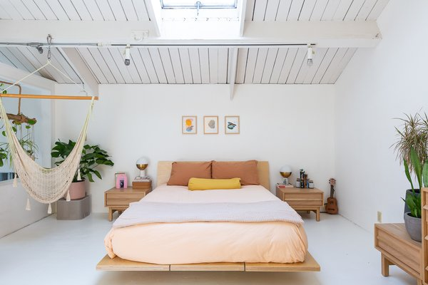 In keeping with the minimal-yet-whimsical aesthetic, a Floyd platform bed takes center stage with a Coyuchi percale duvet and sheets in blush and ginger. Flanking either side are EQ3 Marcel Nightstands from AllModern.