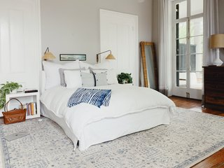 """I tend to keep the color palette pretty simple—whites, neutrals, with some black and blues. I like to layer textures to create a space that feels clean, cozy, and calming,"" says Amanda. An indigo dyed blanket from Mali adds texture atop Serena & Lily bedding in the bedroom."