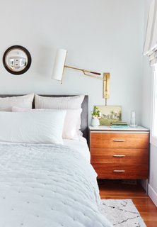 A swinging wall sconce adds a touch of drama and warmth to the bedroom.