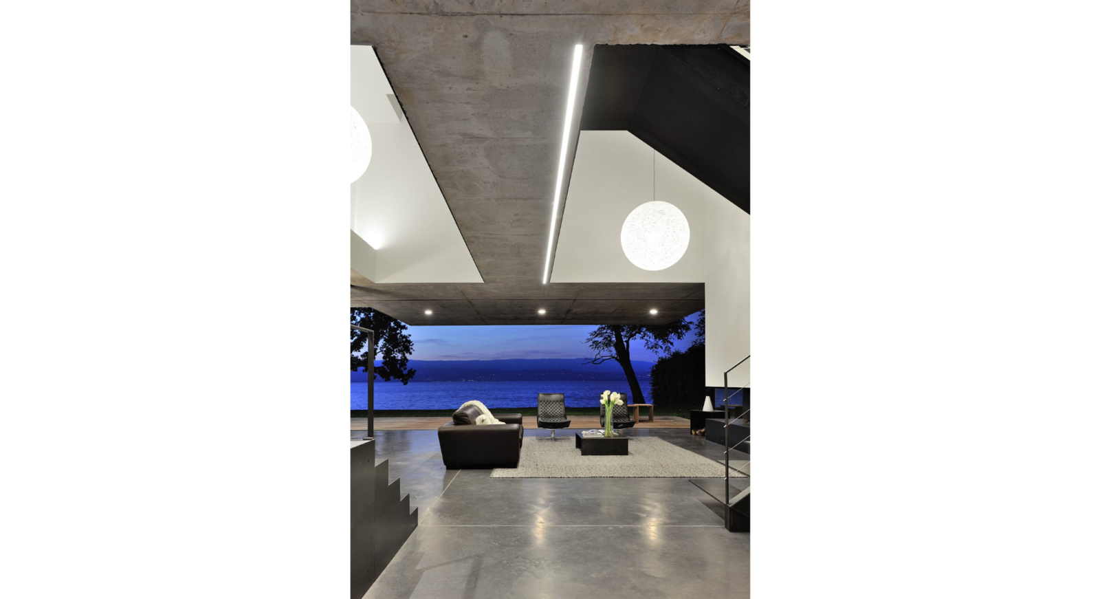 Living Room, Sofa, Coffee Tables, Recliner, Console Tables, Ceiling Lighting, Pendant Lighting, and Concrete Floor Overlooking the setting sun  House on the Lake