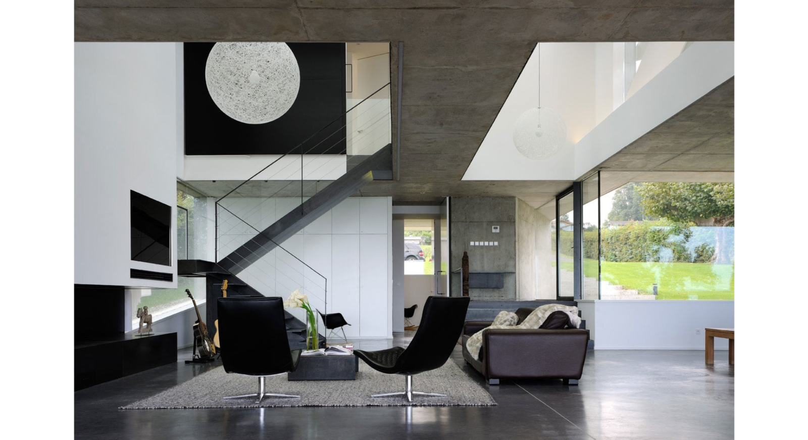 Living Room, Sofa, Recliner, Pendant Lighting, Ceiling Lighting, Coffee Tables, Concrete Floor, and Standard Layout Fireplace The living room and its void   House on the Lake