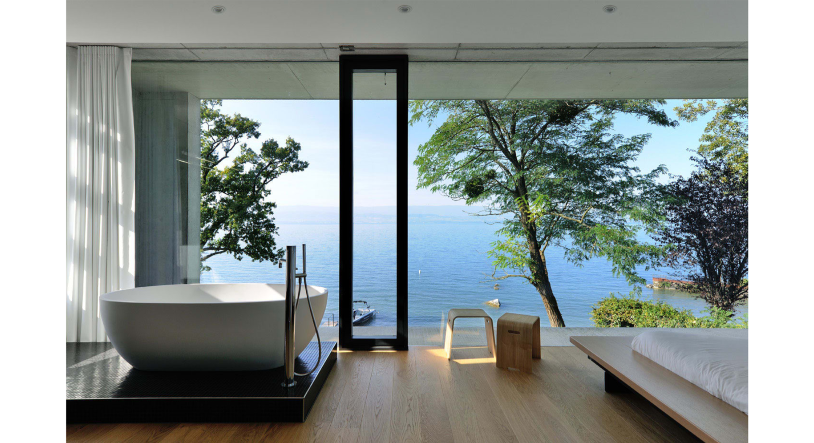 Light Hardwood Floor, Bed, Chair, Ceiling Lighting, Freestanding Tub, Concrete Wall, Tile Counter, Windows, Sliding Window Type, and Metal The bathroom  House on the Lake