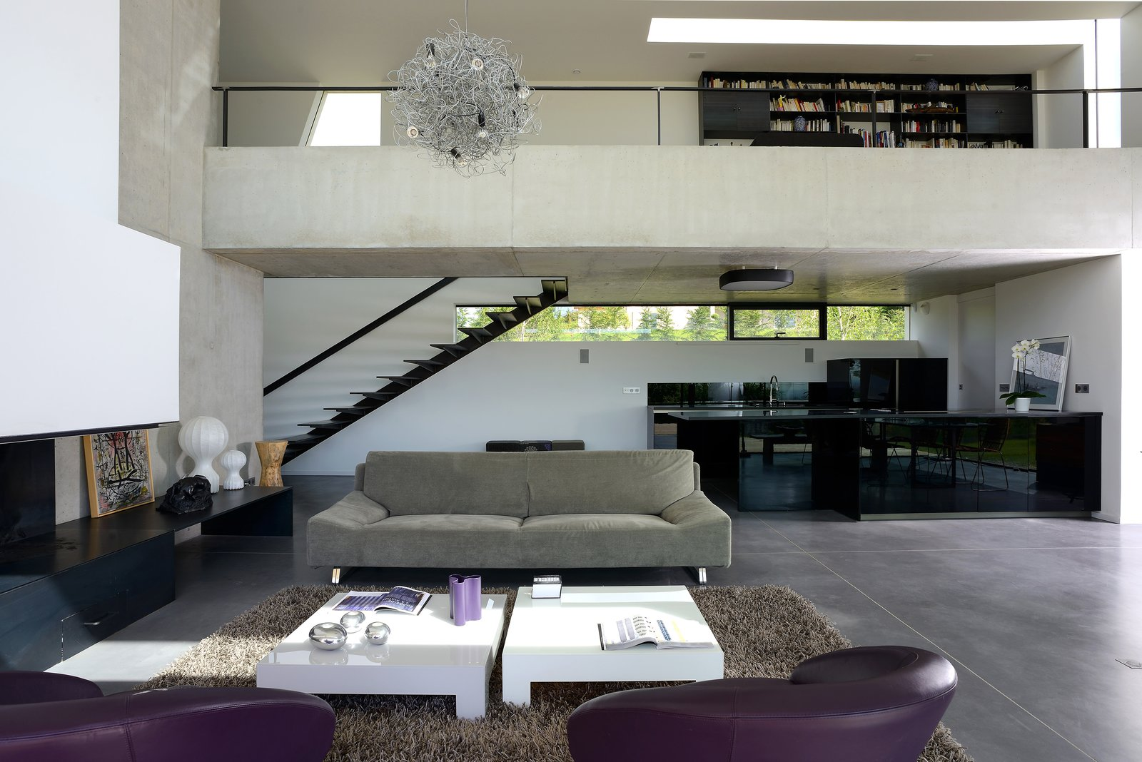 Sofa, Recliner, Chair, Coffee Tables, Ceiling Lighting, Concrete Floor, Standard Layout Fireplace, Staircase, Metal Tread, and Metal Railing the livingroom  Chipster Blister House by AUM Pierre Minassian