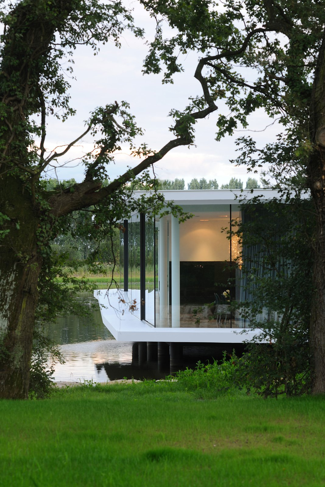 Exterior, House, Flat, Green, Concrete, and Glass The house ontop of the lake  Best Exterior Glass Green Flat Photos from White Snake house