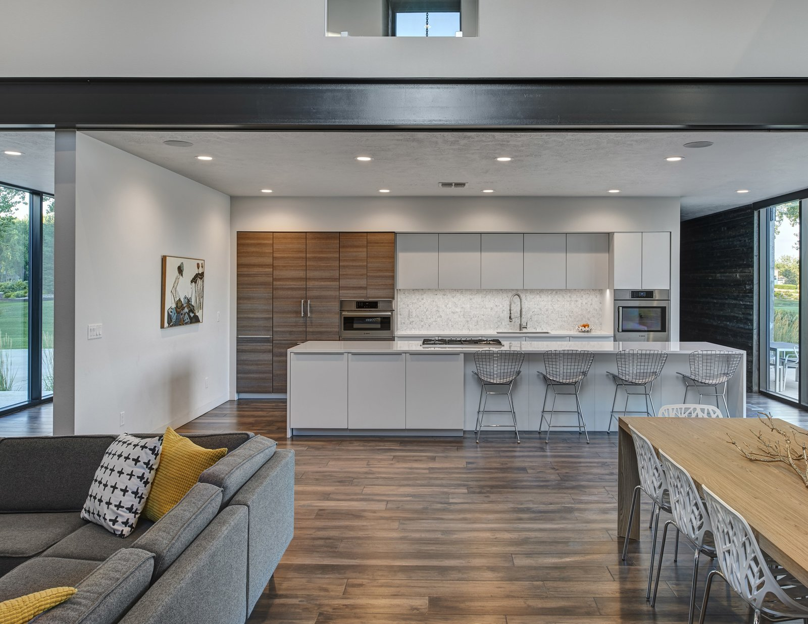 Kitchen, Quartzite Counter, White Cabinet, Wood Cabinet, Recessed Lighting, Refrigerator, Wall Oven, Dark Hardwood Floor, Ceramic Tile Backsplashe, Cooktops, Wine Cooler, Dishwasher, Microwave, and Undermount Sink View of the kitchen. (2017)  530 house