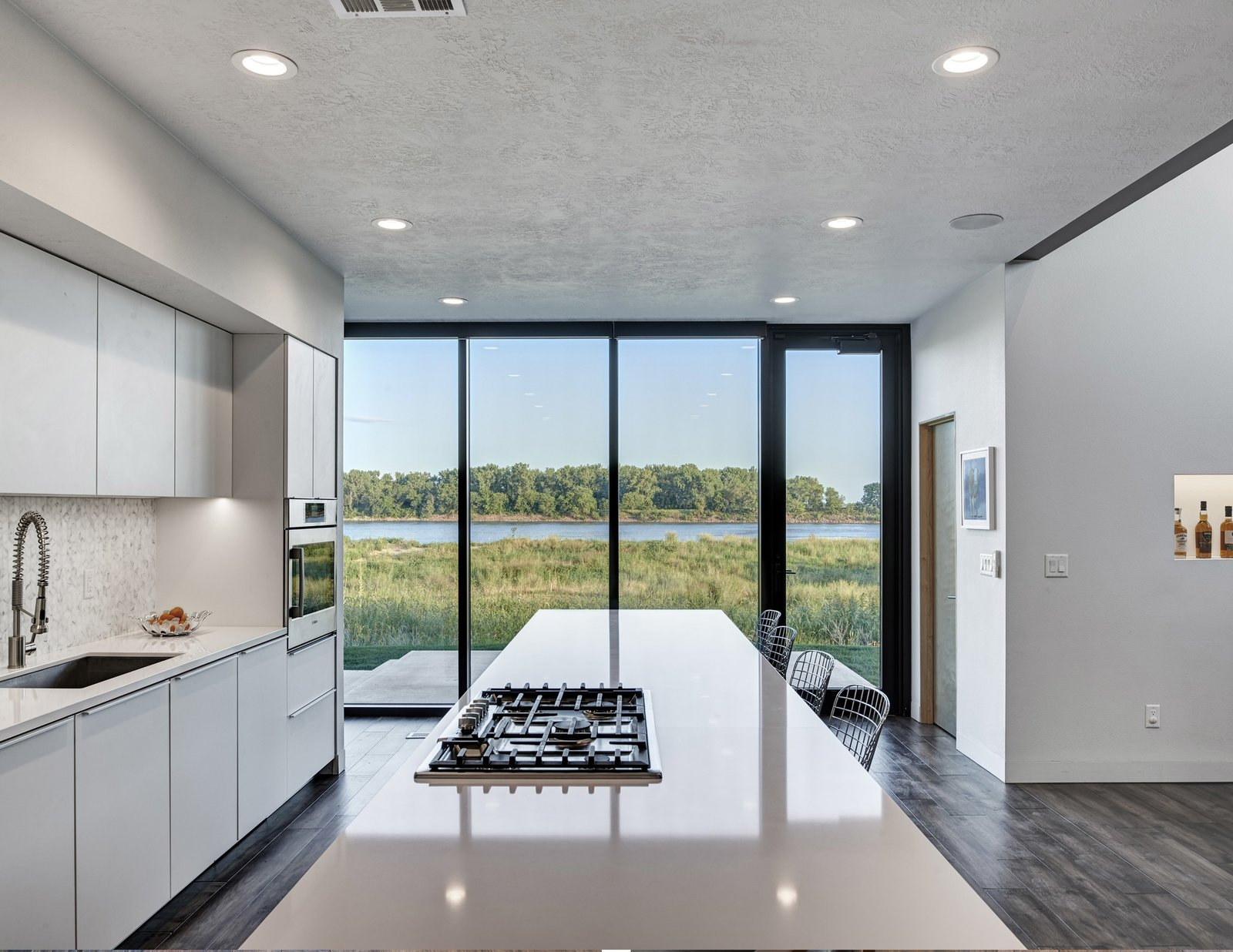 Quartzite Counter, White Cabinet, Dark Hardwood Floor, Ceramic Tile Backsplashe, Wood Cabinet, Recessed Lighting, Wall Oven, Refrigerator, Cooktops, Wine Cooler, Dishwasher, Microwave, Undermount Sink, and Kitchen View to the kitchen island overlooking the Missouri River. (2017)  530 house