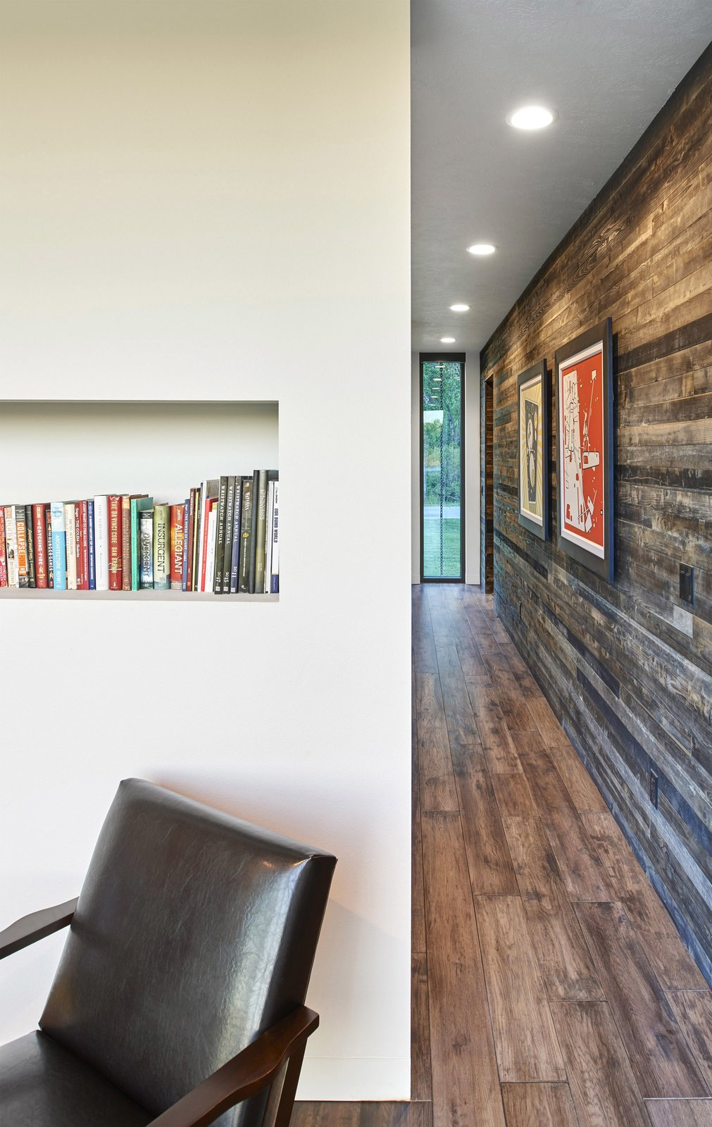 Bookcase, Chair, Recessed Lighting, Dark Hardwood Floor, and Living Room View to the north looking at the reading room on the left and the formerly-exterior cedar sheathed wall at the right. (2017)  530 house