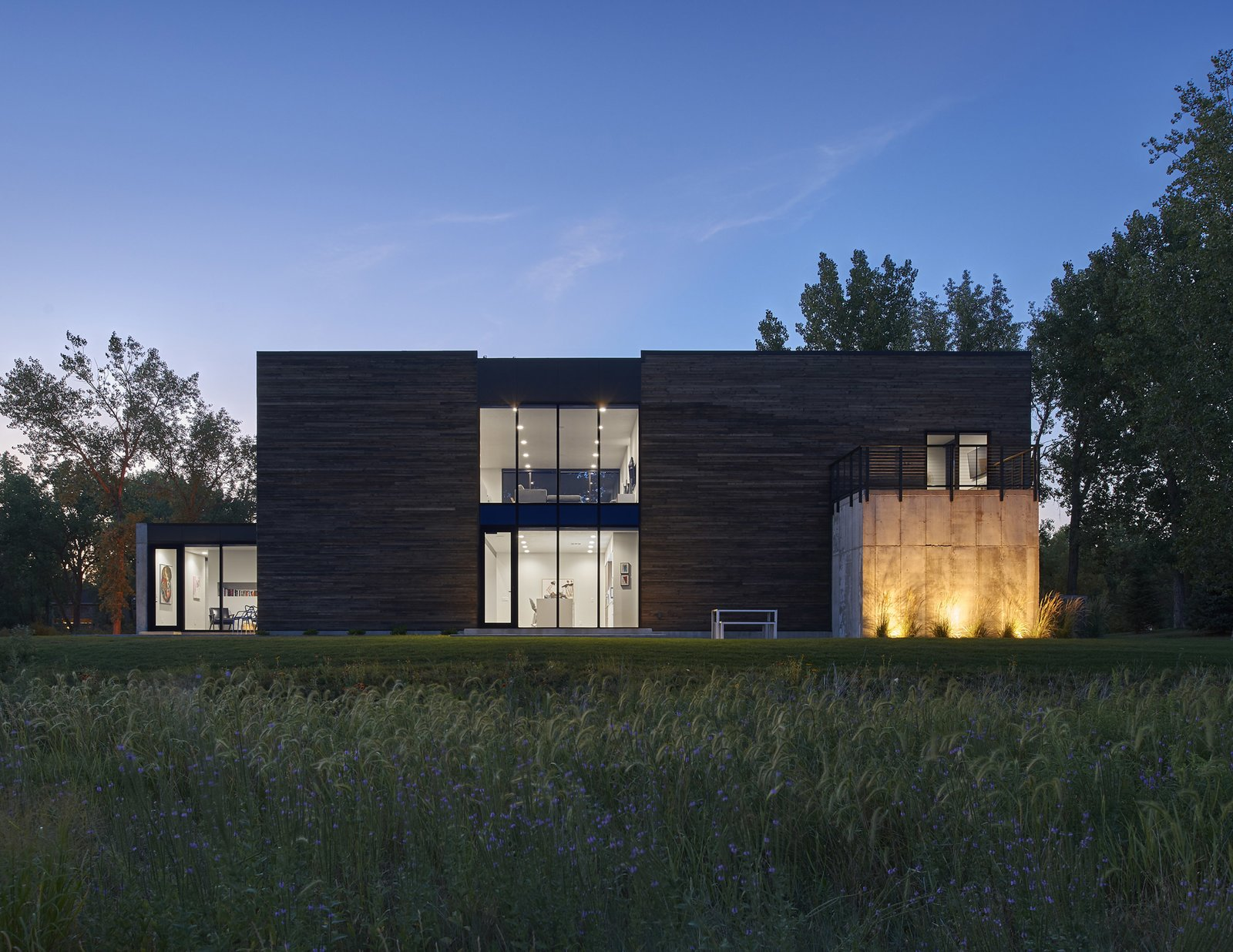 Exterior, House Building Type, Concrete Siding Material, and Wood Siding Material Nighttime view of the south facade (river side) from the prairie.  (2017)  530 house