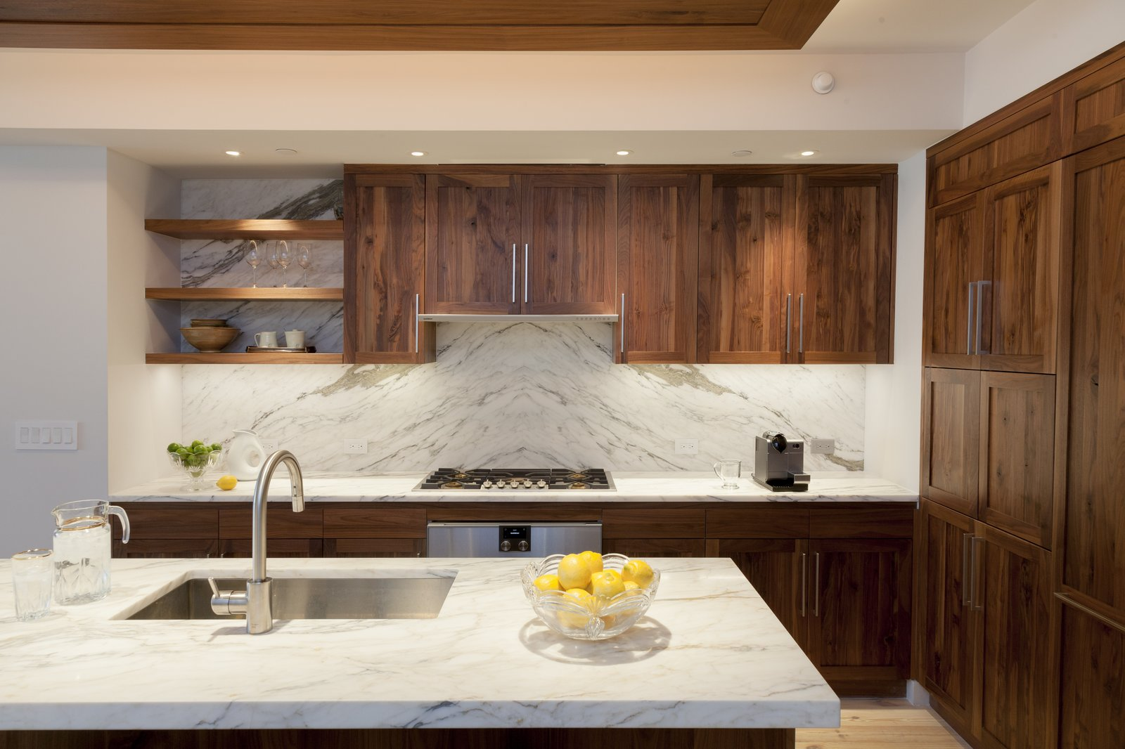 Kitchen, Marble, Wood, Stone Slab, Ceiling, Pendant, Light Hardwood, Accent, Recessed, Refrigerator, Wall Oven, Cooktops, Range, Range Hood, Wine Cooler, Ice Maker, Dishwasher, Microwave, and Undermount Walnut and book-matched  Calcutta kitchen  Best Kitchen Wall Oven Wood Undermount Recessed Range Photos from Pierhouse At Brooklyn Bridge Park Condo