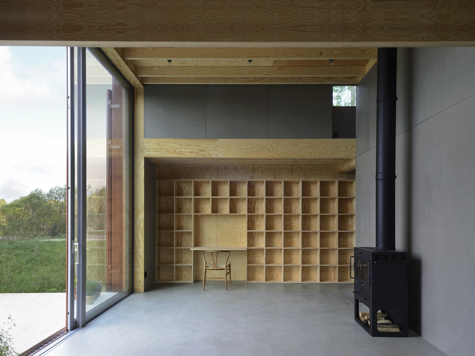 Living room's north side with a built-in bookcase and glass opening to the wide open landscape. Floors of glossy concrete, plywood walls and gray wood fiber boards (type Valchromat), floor tiles and solid plywood furnishings.  Späckhuggaren by Bornstein Lyckefors arkitekter