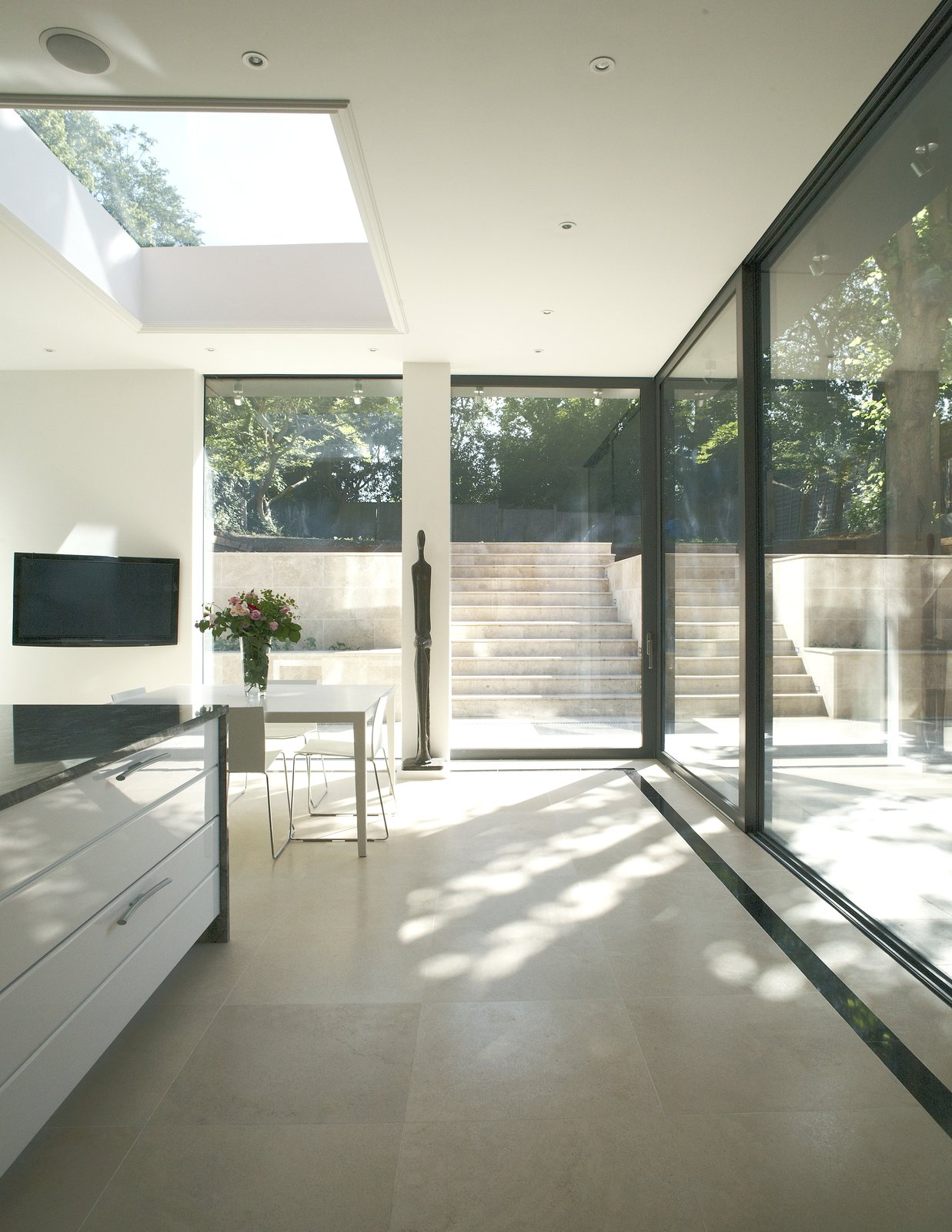 Kitchen, Ceiling, Porcelain Tile, Limestone, and Granite Indside, outside glass doors  Kitchen Limestone Porcelain Tile Photos from Hampstead Home