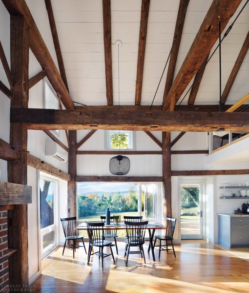Robert Swinburne chose to leave some of the barn's original elements, such as the rustic timber frames. The dining, kitchen, and living areas are now filled with light.