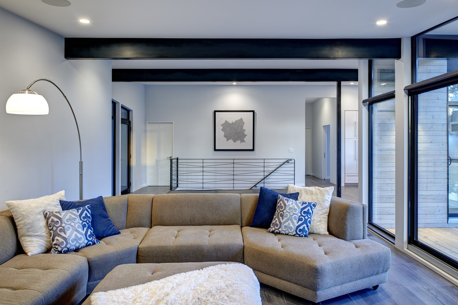 Living Room, Sofa, Ceiling Lighting, Accent Lighting, and Porcelain Tile Floor Black aluminum-covered beams and a clean white ceiling work together to pull the exterior into the living spaces.  Koser I by Neumann Monson Architects
