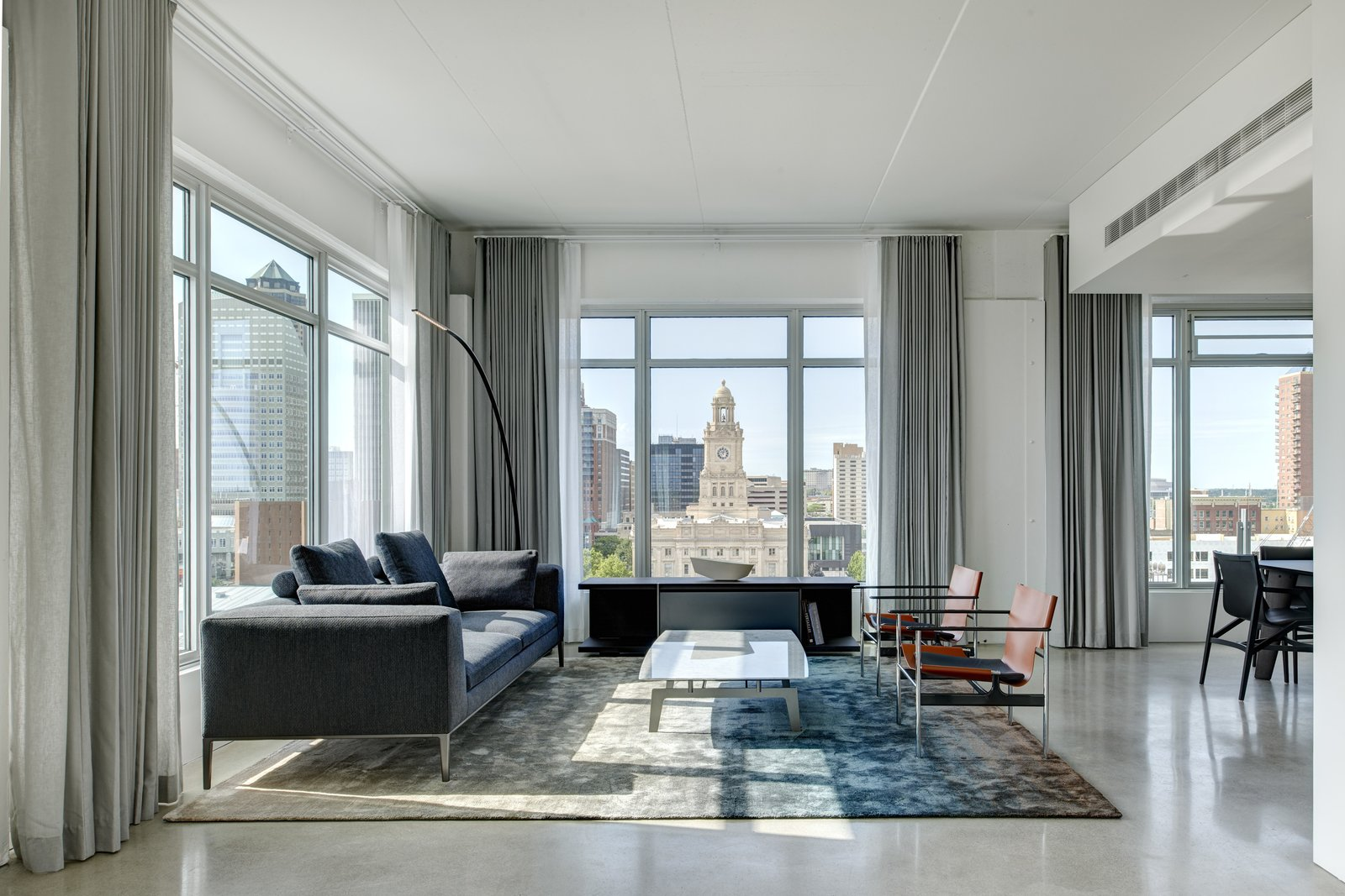 Living Room, Lamps, Storage, Console Tables, Sofa, Chair, Coffee Tables, and Concrete Floor The primary living space is located at the corner of the condo offering views to downtown.  Whiteline Residence by Neumann Monson Architects