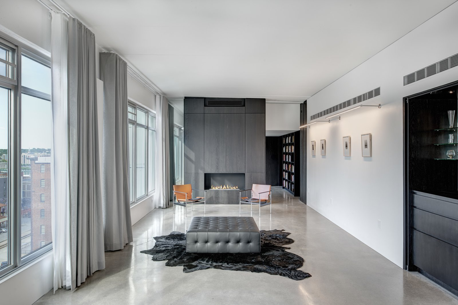Living Room, Gas Burning Fireplace, Concrete Floor, Wall Lighting, Bench, Chair, and Standard Layout Fireplace The gallery contains the clients calligraphic art collection offers views to downtown.  Whiteline Residence by Neumann Monson Architects