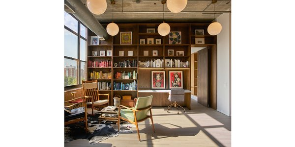 Walnut millwork room divider with adjustable shelves, stone desk and pivot door.