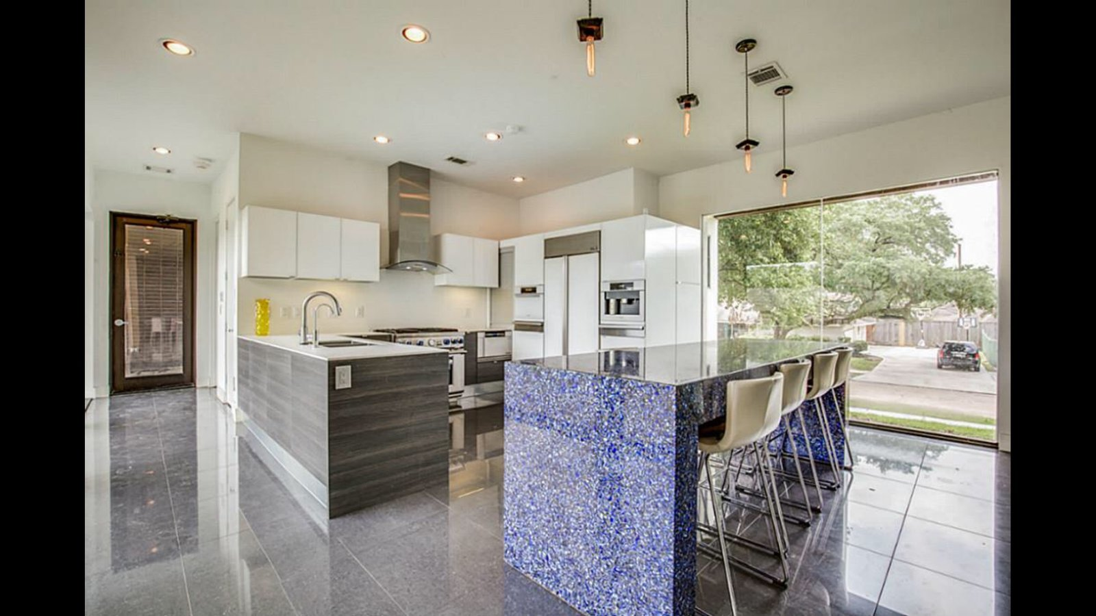 Kitchen, White Cabinet, Ceramic Tile Floor, Ceramic Tile Backsplashe, Ceiling Lighting, Refrigerator, Cooktops, Microwave, and Dishwasher Kitchen with an island of recycled sky blue vodka bottles in concrete.  The Peña Home
